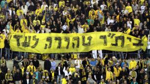 مشجعو فريق بيتار القدس لكرة القدم يرفعون لافتة كتب عليها 'بيتار نقي إلى الأبد'، 26 يناير 2013 (Flash90)