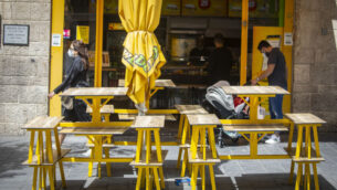 إسرائيليون يرتدون أقنعة الوجه بسبب تفشي فيروس كورونا بالقرب من مطعم مغلق في القدس، 3 مايو 2020 (Olivier Fitoussi / Flash90)