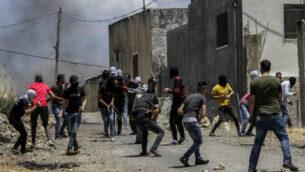 اشتباكات بين فلسطينيين وجنود إسرائيليين خلال احتجاج على خطة إسرائيل لضم أجزاء من الضفة الغربية، في قرية كفر قدوم، بالقرب من مدينة نابلس بالضفة الغربية، 19 يونيو، 2020. (Nasser Ishtayeh / Flash90)