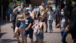 إسرائيليون يرتدون أقنعة واقية في تل أبيب، 25 أغسطس، 2020. (Miriam Alster / Flash90)