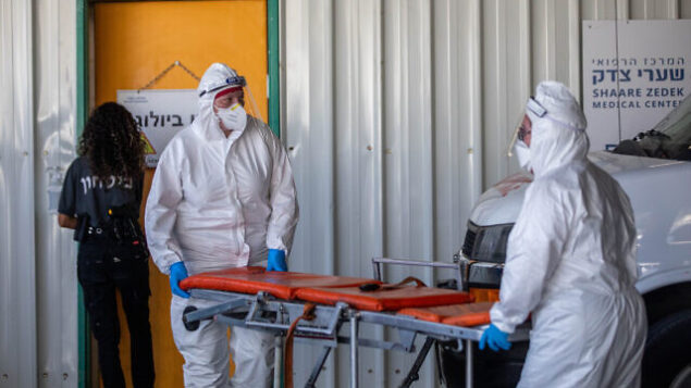 عاملان في نجمة داوود الحمراء لخدمات الإسعاف يرتديان الزي الواقي خارج وحدة فيروس كورونا في مستشفى شعاري تسيدك بالقدس، 6 سبتمبر، 2020. (Yonatan Sindel/Flash90)