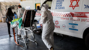 عمال نجمة داوود الحمراء يرتدون ملابس واقية خارج وحدة فيروس كورونا في مستشفى شعاري تسيديك في القدس، 14 سبتمبر 2020 (Nati Shohat / Flash90)