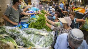 متسوقون إسرائيليون يرتدون الكمامات للوقاية من فيروس كورونا في سوق محانيه يهودا في القدس، 14 سبتمبر، 2020. (Olivier Fitoussi / Flash90)