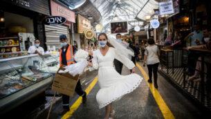 عروس اسرائيلية ترتدي قناع وجه في سوق محانيه يهودا في القدس، 15 سبتمبر 2020 (Yonatan Sindel / Flash90)