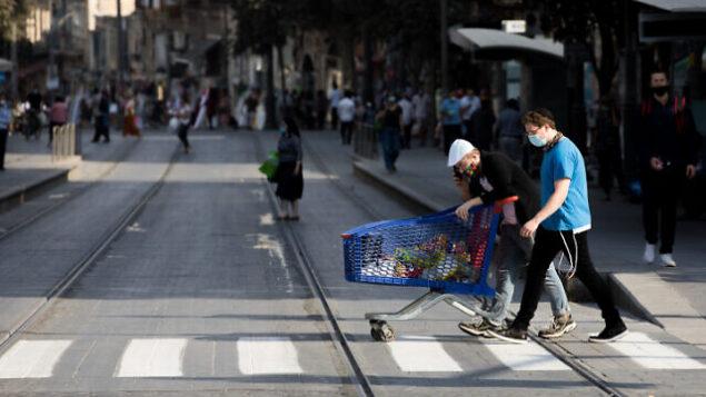 أشخاص يرتدون أقنعة الوجه في شارع يافا في القدس، 17 سبتمبر، 2020. (Nati Shohat / Flash90)