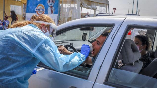 عاملون صحيون من صندوق المرضى 'كلاليت' يأخذون عينات اختبار من إسرائيل في مجمع 'أفحص وسافر' للتحقق مما إذا كانوا مصابين بفيروس كورونا في اللد، 17 سبتمبر، 2020. (Yossi Aloni / FLASH90)