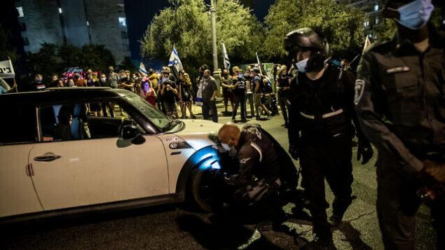 عناصر من الشرطة يفتشون سيارة رجل اندفع باتجاه الشرطة والمتظاهرين خلال مظاهرة ضد رئيس الوزراء بنيامين نتنياهو، خارج مقر إقامته الرسمي في القدس، 20 سبتمبر 2020 (Yonatan Sindel / Flash90)