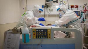 عمال الرعاية الصحية يرتدون زيا واقيا أثناء عملهم في جناح فيروس كورونا في مستشفى شعاري تسيدك في القدس، 23 سبتمبر، 2020. (Nati Shohat / Flash90)