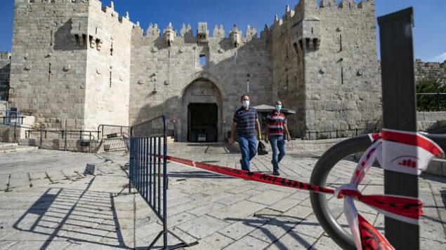 أشخاص يسيرون خارج باب العامود إلى البلدة القديمة في القدس، 25 سبتمبر، 2020، وسط إغلاق على مستوى البلاد بسبب فيروس كورونا. (Olivier Fitoussi / Flash90)