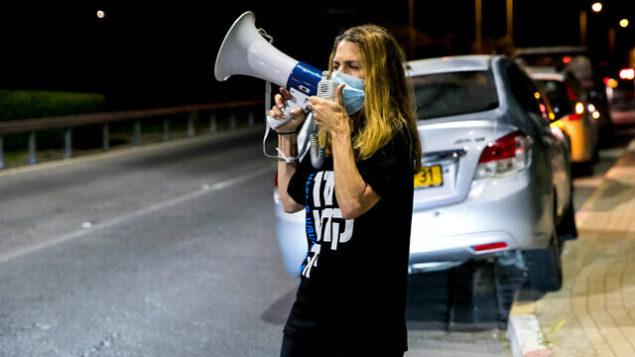 إسرائيليون يتظاهرون ضد رئيس الوزراء الإسرائيلي بنيامين نتنياهو بالقرب من منزله في قيسارية، 26 سبتمبر، 2020. (Anat Hermony / Flash90)
