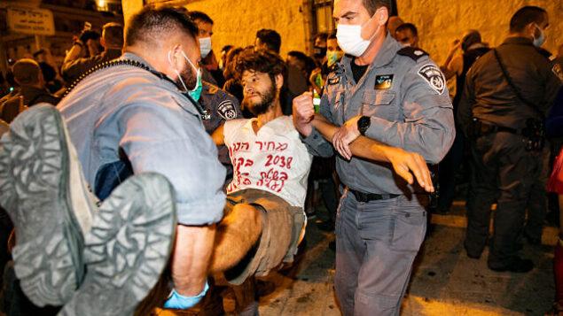 الشرطة تبعد متظاهرين قاموا بسد الطريق خلال مظاهرة ضد رئيس الوزراء بنيامين نتنياهو أمام مقر أقامته الرسمي في القدس، 20 سبتمبر، 2020. (Olivier Fitoussi/Flash90)