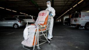 عامل في نجمة داوود الحمراء يرتدي ملابس واقية خارج وحدة فيروس كورونا في مستشفى شعاري تسيدك في القدس، 24 سبتمبر، 2020. (Yonatan Sindel / Flash90)