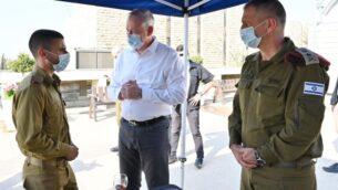 وزير الدفاع بيني غانتس، وسط الصورة، يتحدث إلى ضابط في الجيش الإسرائيلي بينما قائد الجيش اللفتنانت جنرال أفيف كوخافي يراقبهما، خلال زيارة للقيادة المركزية للجيش الإسرائيلي في القدس، 15 سبتمبر 2020 (Ariel Hermoni / Defense Ministry)