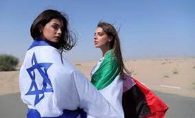 عارضة الأزياء الإسرائيلية ماي تاغر، من اليسار، تغطي نفسها بالعلم الإسرائيلي، وإلى جانبها تقف أناستازيا باندارينكا، عارضة أزياء مقيمة في الإمارات والتي تغطي نفسها بالعلم الإماراتي، في جلسة تصوير في دبي، الإمارات العربية المتحدة، الأحد، 8 سبتمبر، 2020. (Kamran Jebreili / AP)