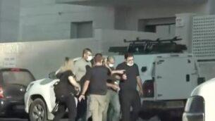 وليد منصور، في وسط الصورة، مكبل اليدين، يعيد تمثيل هجوم الطعن المزعم ضد رجل إسرائيلي في موقف بناء بمدينة روش هعاين.  (Channel 12 news)