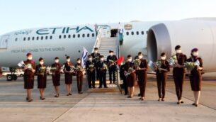 طاقم طائرة شركة 'الاتحاد' يلوحون بالأعلام الإسرائيلية بعد الهبوط في مطار بن غوريون، 19 أكتوبر 2020 (Sivan Farag)