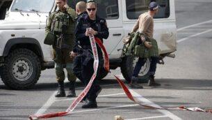 توضيحية: شرطة وجنود اسرائيليون يتفقدون موقع هجوم طعن فاشل في مفترق 'الياس' بالقرب من الخليل ومستوطنة كريات اربع في الضفة الغربية، 5 نوفمبر، 2018. (HAZEM BADER / AFP)
