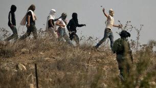 توضيحية: جنود إسرائيليون يقفون في موقف المتفرج بينما يقومو مستوطنون ملثمون بإلقاء الحجارة على متظاهرين فلسطينيين (لا يظهرون في الصورة) خلال مظاهرة ضد البناء في بؤرة استيطانية إسرائيلية بالقرب من قرية ترمسعيا الفلسطينية ومستوطنة شيلو، شمال رام الله في الضفة الغربية، 17 أكتوبر، 2019. (JAAFAR AshHTIYEH / AFP)