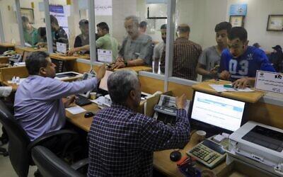 فلسطينيون يتلقون مساعدات مالية من قطر في مكتب بريد في مدينة غزة، 27 يونيو، 2020. (Mahmud Hams / AFP)