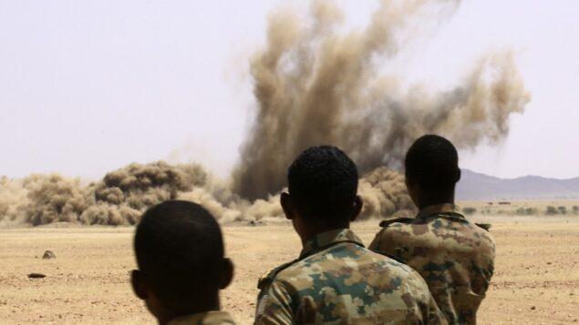 عناصر من الجيش السوداني يقفون بينما يتم تدمير أسلحة جُمعت من مواطنين سودانيين في قاعدة حجر العسل بولاية نهر النيل على بعد 200 كيلومتر شمال العاصمة الخرطوم، 29 سبتمبر 2020 (ASHRAF SHAZLY / AFP)
