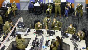 أعضاء من فرقة العمل الإسرائيلية للاستجابة لكوفيد-19 ، وهي جزء من قيادة الجبهة الداخلية للجيش الإسرائيلي ، يحضرون اجتماعا في مقر إدارة الأزمات في الرملة، 30 سبتمبر 2020. (Emmanuel DUNAND / AFP)