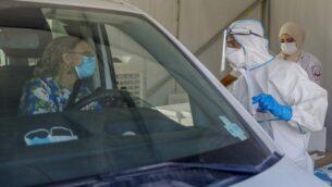 مسعف مع نجمة داوود الحمراء للخدمات الطبية يتحدث مع سائق في مركز اختبار لكوفيد-19 في القدس، 7 أكتوبر 2020 (AHMAD GHARABLI / AFP)