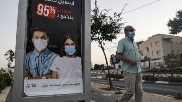 رجل يمر بجانب لافتة اعلانية نشرتها وزارة الصحة الاسرائيلية باللغة العربية تطالب المواطنين بارتداء الكمامات كوسيلة للوقاية من مرض فيروس كورونا كوفيد-19 في حي في الشيخ جراح في القدس الشرقية، 8 أكتوبر، 2020. (Ahmad GHARABLI / AFP)