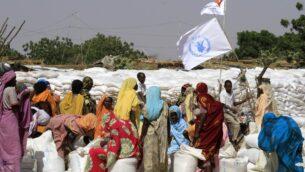 في هذه الصورة من الأرشيف التي التقطت في 6 نوفمبر 2014، نازحات سودانيات يقمن بجمع مساعدات إنسانية مقدمة من برنامج الغذاء العالمي التابع للأمم المتحدة، في مخيم كلمة للنازحين داخليا الواقع شرق مدينة نيالا بدارفور السودان. برنامج الغذاء العالمي. ( Ashraf SHAZLY / AFP)