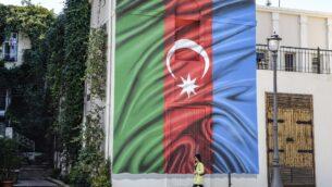 امرأة تمر من أمام مبنى عليه رسم العلم الأذربيجاني على جداره في باكو، وسط النزاع العسكري المستمر بين أرمينيا وأذربيجان حول منطقة ناغورني قره باغ الانفصالية، 14 أكتوبر 2020 (TOFIK BABAYEV / AFP)
