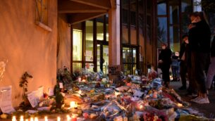 يقف الناس أمام الزهور والشموع بجوار لافتة كتب عليها 'أنا مدرس، أنا صموئيل' عند مدخل مدرسة إعدادية في كونفلانس سانت أونورين، 30 كم شمال غرب باريس، 17 أكتوبر 2020 (BERTRAND GUAY / AFP)