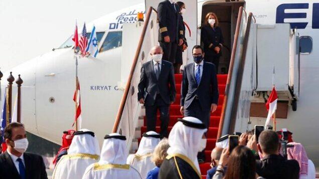 مستشار الأمن القومي مئير بن شبات (يسار) ووزير الخزانة الأمريكي ستيف منوشين ينزلان من طائرة لدى وصولهما مطار البحرين الدولي، 18 أكتوبر، 2020. (Ronen Zvulun / Pool / AFP)