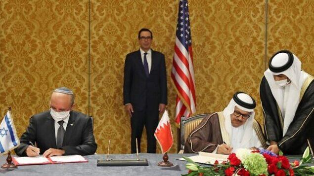رئيس الوفد الإسرائيلي، مستشار الأمن القومي مئير بن شبات (إلى اليسار)، ووزير الخارجية البحريني عبد اللطيف بن راشد الزياني، يوقعان على اتفاق إسرائيلي بحريني لإضفاء الطابع الرسمي على العلاقات الدبلوماسية، في العاصمة البحرينية المنامة، 18 أكتوبر، 2020. بينهما يقف وزير الخزانة الأمريكي ستيف منوشين. (Ronen Zvulun/Pool/AFP)