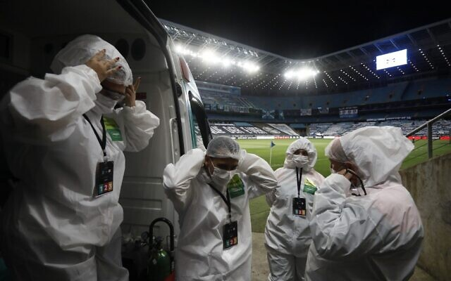 مسعفون يرتدون بدلات واقية وسط جائحة فيروس كورونا الجديد في ملعب أرينا دو جريميو الفارغ في بورتو أليجري بالبرازيل، 22 أكتوبر 2020 (DIEGO VARA / POOL / AFP)