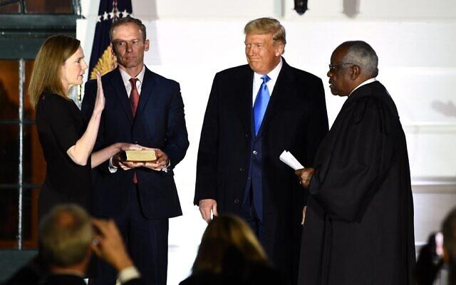 الرئيس الأمريكي دونالد ترامب أثناء أداء القاضية إيمي كوني باريت اليمين كقاضية في المحكمة العليا الأمريكية، الى جانب زوجها جيسي إم باريت، خلال احتفال في الحديقة الجنوبية للبيت الأبيض، في واشنطن العاصة، 26 أكتوبر 2020 (Brendan Smialowski / AFP)