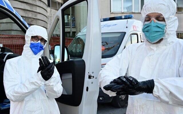 عاملون طبيون في منطقة فحص كوفيد-19 بالسيارة في منطقة الفرز بمستشفى سان كارلو في ميلانو، إيطاليا، 28 أكتوبر 2020. (MIGUEL MEDINA / AFP)
