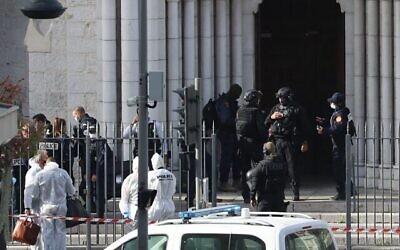 عناصر شرطة فرنسية من وحدة النخبة RAID تدخل كنيسة  نوتردام  في نيس بينما ينتظر عناصر شرطة التحليل الجنائي في الخارج بعد هجوم بسكين وقع في المكان، نيس، 29 أكتوبر، 2020. (Valery HACHE / AFP)