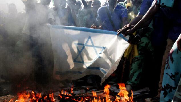 طلاب سودانيون يحرقون العلم الإسرائيلي في مظاهرة ضد الضربات الجوية الإسرائيلية في غزة أمام مقر الأمم المتحدة في الخرطوم، السودان، 29 ديسمبر، 2008. (AP / Abd Raouf)