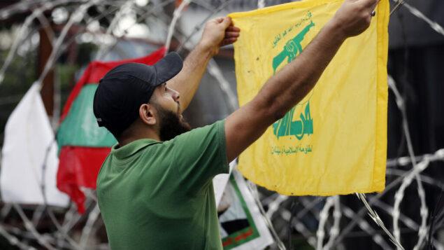 أحد مؤيدي حزب الله يهتف شعارات وهو يرفع علم حزبه خلال احتجاج على التدخل الأمريكي في شؤون لبنان، بالقرب من السفارة الأمريكية في عوكر، شمال شرق بيروت، لبنان، 10 يوليو 2020 (AP Photo / Hussein Malla)