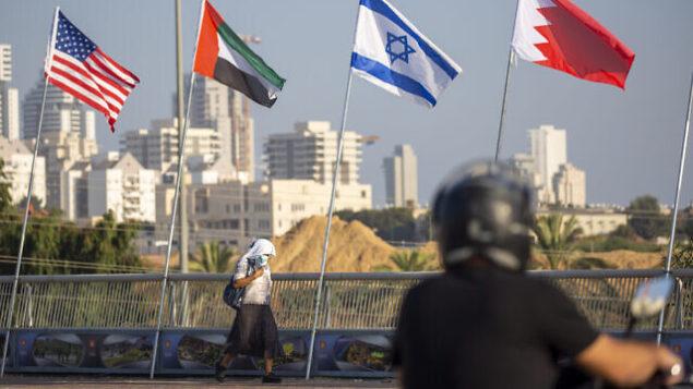 امرأة ترتدي كمامة للوقاية من جائحة كورونا تمر أمام أعلام الولايات المتحدة والإمارات العربية المتحدة وإسرائيل والبحرين عند جسر السلام في نتانيا، إسرائيل، 14 سبتمبر، 2020. (AP / Ariel Schalit)