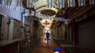 رجل يسير في سوق مغلق وسط إغلاق كامل فرضته السلطات بسبب فيروس كورونا، في تل أبيب، 18 سبتمبر، 2020. (AP Photo / Oded Balilty)