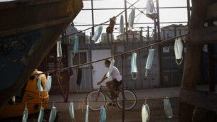 رجل يرتدي قناعا للوجه يركب دراجته بجانب قوارب تم تعليق كمامات عليها خلال إغلاق في جميع أنحاء البلاد للحد من انتشار فيروس كورونا، في ميناء يافا بالقرب من تل أبيب، 7 أكتوبر ، 2020. (Oded Balilty / AP)