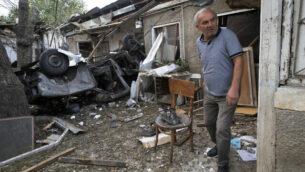 رجل يسير في ساحة منزل دمره قصف مدفعي أذربيجان خلال صراع عسكري في ستيباناكرت  بمنطقة ناغورنو كاراباخ الانفصالية، 9 أكتوبر، 2020. (AP Photo)