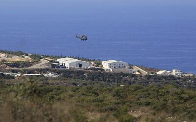 مروحية تحلق فوق قاعدة لقوة حفظ السلام التابعة للأمم المتحدة في بلدة الناقورة جنوب لبنان، خلال الجولة الأولى من المحادثات بين الوفدين اللبناني والإسرائيلي، 14 أكتوبر 2020 (AP/Bilal Hussein)