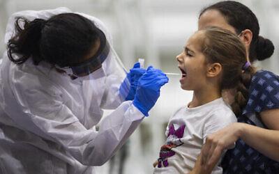 فتاة صغيرة تخضع لفحص فيروس كورونا من قبل عاملة رعاية صحية في مركز اختبار كوفيد-19 أقيم في ملعب كرة سلة في رمات غان، 20 أكتوبر 2020 (AP Photo / Oded Balilty)