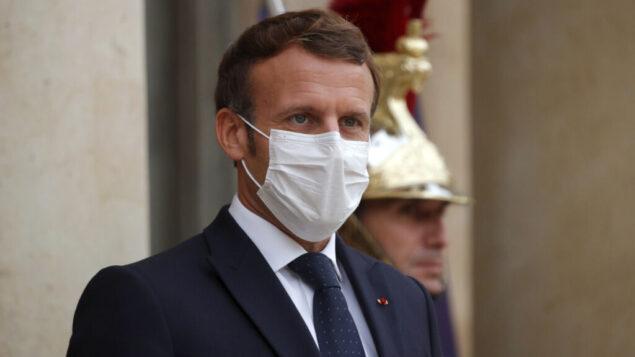 الرئيس الفرنسي إيمانويل ماكرون، يرتدي قناع الوجه الواقي، وينتظر الترحيب بالرئيس الأرميني أرمين سركيسيان لحضور اجتماع في قصر الإليزيه في باريس، 22 أكتوبر 2020. (Charles Platiau / Pool via AP)