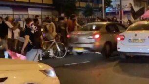لقطة شاشة من مقطع فيديو لسيارة ، وسط الصورة ، وهي تصطدم بمتظاهرين مناهضين للحكومة خلال مظاهرة في تل أبيب، 1 أكتوبر ، 2020. (Twitter)
