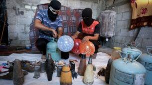 فلسطينيون في مدينة رفح جنوب غزة يعدون بالونات حارقة لإطلاقها باتجاه إسرائيل، 8 أغسطس 2020 (Abed Rahim Khatib / Flash90)