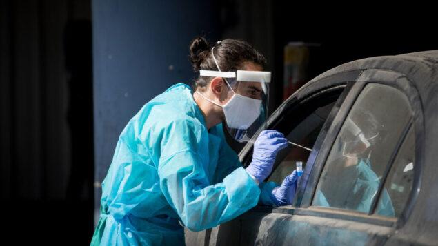 عامل طبي في مستشفى شعاريه تسيديك في القدس يأخذ مسحة من شخص لاختبار فيروس كورونا، 30 سبتمبر 2020. (Nati Shohat / Flash90)