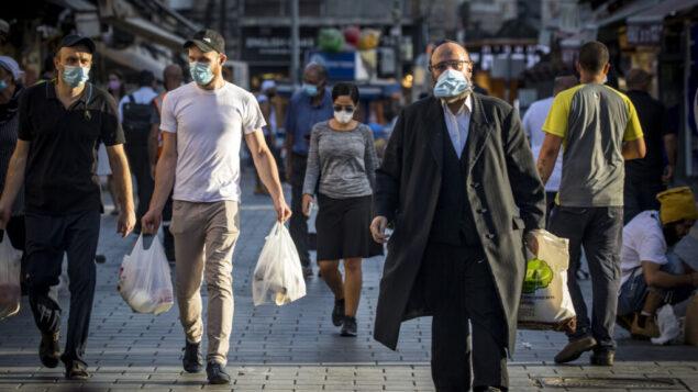 اشخاص يرتدون أقنعة الوجه في سوق محانيه يهودا في القدس، 30 سبتمبر 2020، خلال إغلاق على مستوى البلاد لمنع انتشار كوفيد-19. (Olivier Fitoussi / Flash90)