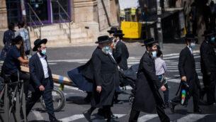 أشخاص يسيرون في حي مئة شعاريم اليهودي المتشدد في القدس، 1 أكتوبر 2020 (Yonatan Sindel / Flash90)